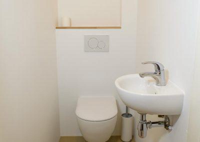Hangend toilet met inbouw reservoir en een wastafel in kleine wc ruimte