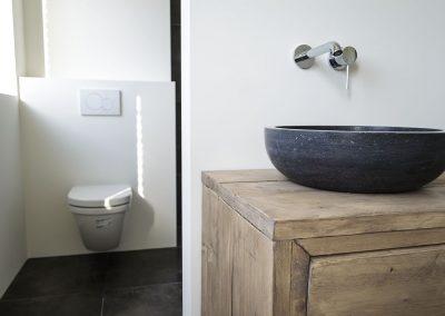 Stenen waskom met badkamermeubel van steigerhout en hang wc