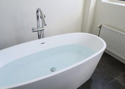 Vrijstaand bad met water en antraciet vloertegel