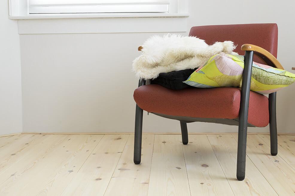 Rode stoel op een grenen vloer met hard wax