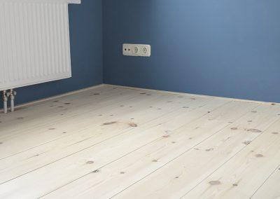 Grenen vloer met hard wax en een blauwe muur