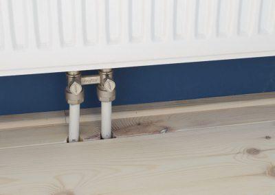 Uitspaaring radiatorleiding in de grenen vloer