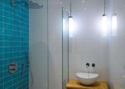 Badkamer met turquoise keramische tegels, inbouw regendouche en waskom