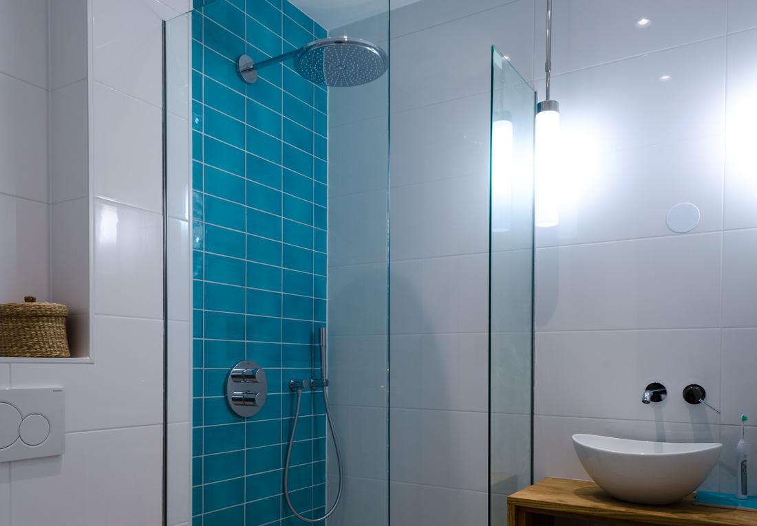 Badkamer met turquoise keramische tegels en inbouw regendouche